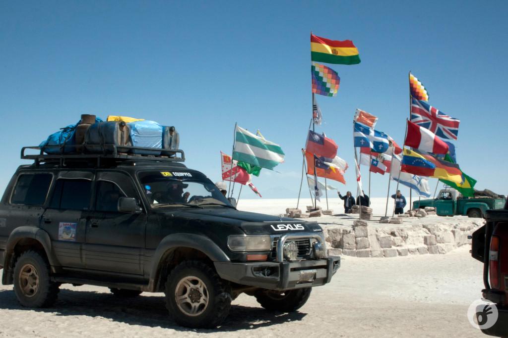 A Wiphala em sua versão tradicional (quadriculada), que ilustra o início do nosso texto de hoje, e possui algumas versões diferentes, dependendo da região andina representada. Nessa foto, aparece por duas vezes (abaixo da bandeira boliviana, e acima da bandeira britânica).